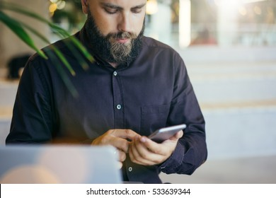Front view. Young bearded businessman in brown shirt uses smartphone. Man looks at screen of smartphone in his hands. Guy chatting, browsing internet, checking email on digital gadget