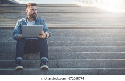 Front view. Young bearded businessman sitting outdoor on steps and using laptop. Hipster man is working, blogging, chatting online,checking email. Student learning online. Summer sunny day. Lifestyle.