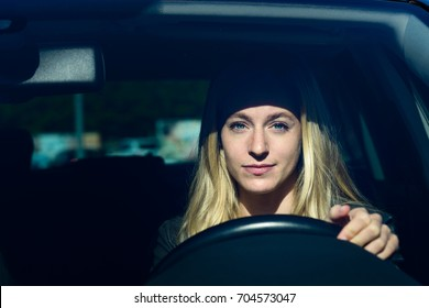 Front view of young blond woman smiling while driving car