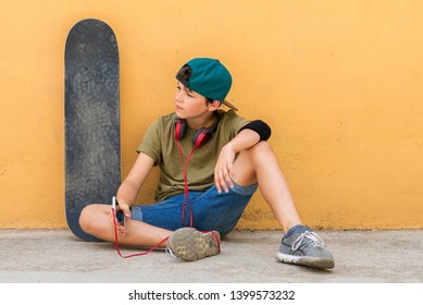 Front view of a young boy sitting on ground leaning on a yellow wall while using a mobile phone to listening music