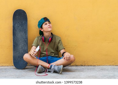 Front view of young boy sitting on ground leaning on a yellow wall while using a mobile phone to listening music