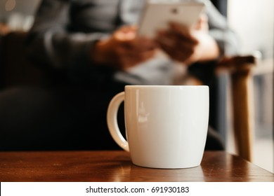 front view. young business man holding tablet for checking stock graph. have coffee cup with coffee putting on table front of him. image for beverage,technology,mobile,body part concept