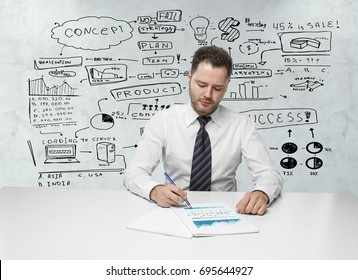 Front view of young businessman doing paperwork at white desk with business sketch in the background. Research concept