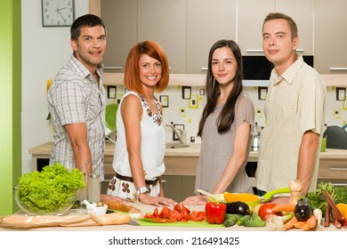 front view of young caucasian friends standing in the kitchen and smiling, with vegetables on table