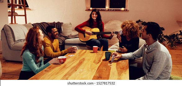 Front view of a young Caucasian woman playing guitar with a group of four young multi-ethnic male and female friends sitting around a table listening and drinking coffees in the sitting room of an