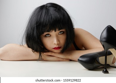 Front view of young Chinese woman with short hair posing on the white background. Isolated.