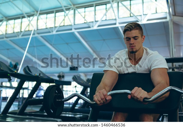 Front view of young concentrated Caucasian male athletic exercising with barbell on preacher bench in fitness center. Bright modern gym with fit healthy people working out and training