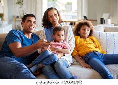 Front view of young family sitting together on the sofa in their living room watching TV, close up, front view