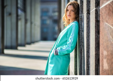 Front view. Young fashionable woman. In the background concrete wall.