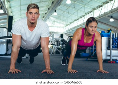 Front view of young fit Caucasian male and female athletic exercising together in fitness center. They are planking in push up pose. Bright modern gym with fit healthy people working out and training