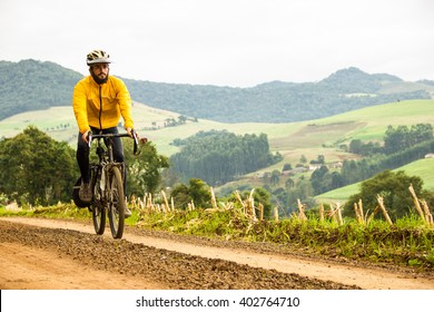Front View of a Young Man With Bicycle on unpaved beautiful road in Brazil. Healthy Lifestyle Concept. Copyspace.