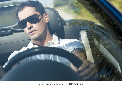 Front view of a young man driving his convertible car