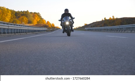 Front view of young man in helmet riding fast on modern sport motorbike at highway. Motorcyclist racing his motorcycle on country road. Guy driving bike during trip. Concept of freedom and adventure.