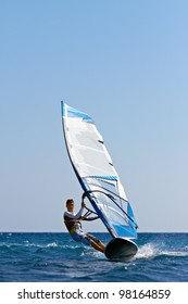 Front view of young man surfing the wind on summer day