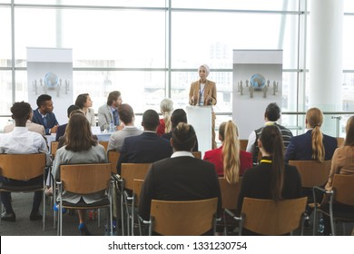 Front view of young mixed race female speaker speaking in a business seminar in modern office building