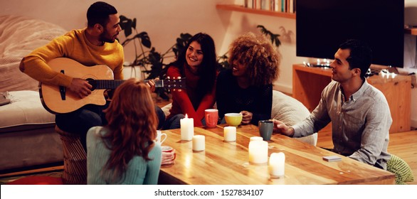 Front view of a young mixed race man playing guitar with a group of four young multi-ethnic male and female friends sitting around a table listening and drinking coffees in the sitting room of an
