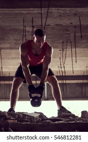 Front view of a young muscular athlete working out, lifting a kettlebell weight in an abandoned ruined building