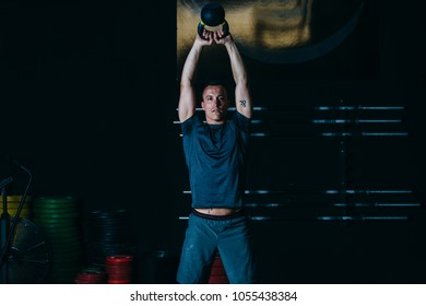 Front view of a young sporty man doing kettlebell swing exercise on a fitness routine at the box gym