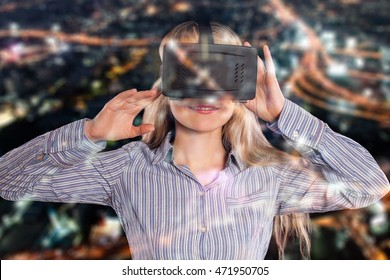 Front view of a young woman with blond hair using the virtual reality headset on black background.