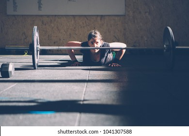Front view of a young woman doing bar facing burpees while is on the floor on a fitness routine at the box gym