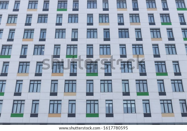 Front wall of an office building with windows and colored tiles