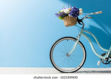 front wheel of bicycle with flowers in basket in front of blue wall