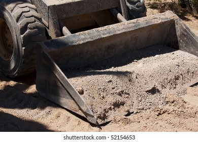 Front wheel loader scoop with load of soil and rocks.