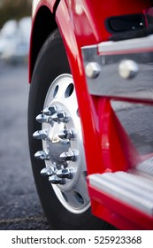 The front wheel of the powerful semi with aluminum rim and chrome mounting bolts and another details of a modern red semi truck.
