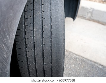 Front wheel tires or tyres on car badly worn and bald because of poor tracking or alignment of the wheels