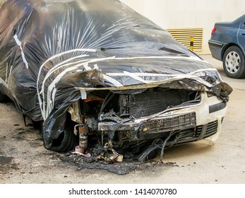 Front wheels, hood and bumper of a car suffered during a fire. Damaged car covered with a film on a city street. Accident, arson or vandalism. Property damaged by fire.