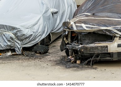 Front wheels, hoods and bumpers of two cars suffered during a fire. Damaged cars covered with a film on a city street. Accident, arson or vandalism. Property damaged by fire.