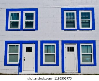 Front of a white brick townhome with blue trim around the windows and doors.