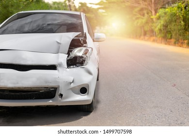 Front of white color car have big damaged and broken by accident on road in morning time can not drive any more park for wait insurance officer. With copy space for text or design