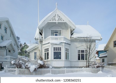 front of a white wooden house covered in snow in Tromso, Norway