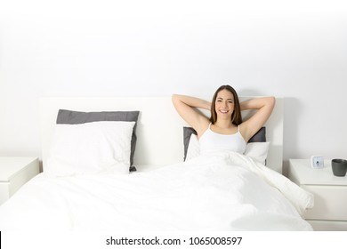 Front wide angle view portrait of a happy woman looking at camera relaxing on the bed with a isolated space above