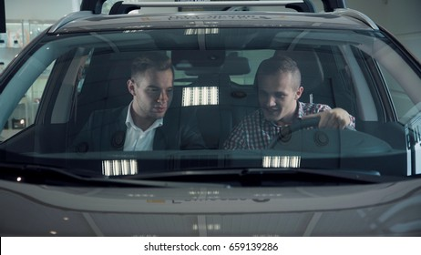 Front window of brand new automobile with lights reflecting on glass in showroom. The buyer and seller are sitting down in the car. The seller says about the new car sitting in the cabin