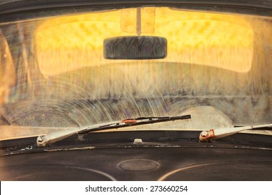 Front window of a dirty old black car with rusted screen wipers