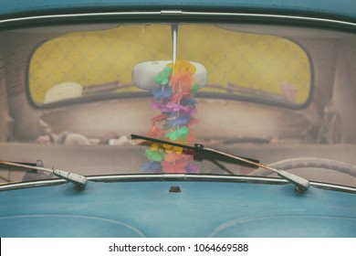 Front window of a dirty old blue car with rusted windshield wipers
