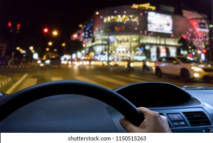 the front window view of the car and blurred image of the city and the road at night with the crosswalk