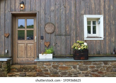 The front of the wooden house with doors, white window and flowers