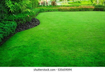 The front yard in spring garden landscape design with tall and short shrubs and flowers has a beautiful rounded shape in the middle is grass multicolored shrubs intersecting bright green grass,Lawn.