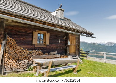 Front yard with wooden table of shepherd lodge on a highland pasture with Alpine mountain landscape in Western Carinthia, Austria.