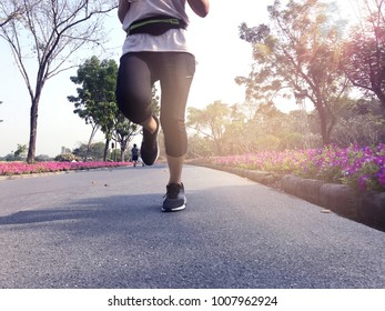 Front of young woman running on the road in the park with sunshine morning,copy space