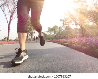 Front of young woman running on the road in the park with sunshine morning, copy space