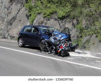 Frontal car accident with motorbike and car on the road. Massive motorcycle crash collision hit by car following a risky road overtaking. Road tragedy with a centaur seriously injured by high speed