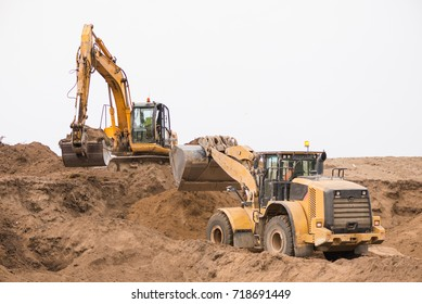 Frontal excavator pushing a gravel pile around at a quarry site