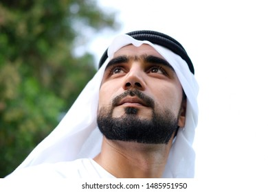 Frontal face of Arabic male camera below his chin while wearing hair veil for Middle Eastern Men