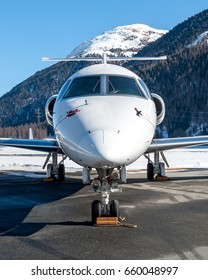 Frontal nose of this white and big Bizjet, private aircraft, on ground in an airport over the snowed mountain. Wheel are locked and the pitot protection inserted. Clear and blu sky, weather cavok.