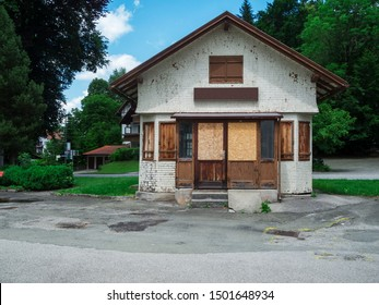 Frontal overall view of an old small station kiosk closed with boards and wooden boards with forecourt in rural Bavarian environment with blue sky.