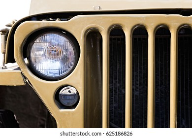 Frontal partial view of a radiator guard or grill and a headlight of vintage sand colored military off road car.